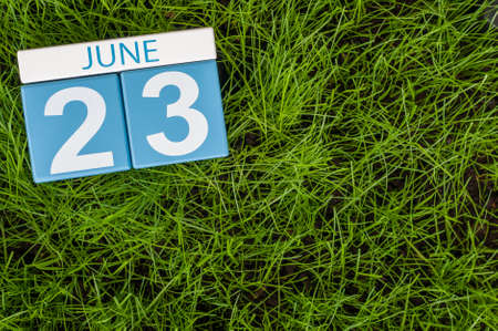 20 23 years: June 23rd. Image of june 23 wooden color calendar on greengrass lawn background. Summer day, empty space for text.