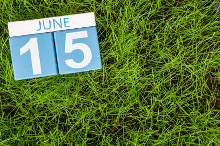 greengrass: June 15th. Image of june 15 wooden color calendar on greengrass lawn background. Summer day, empty space for text.