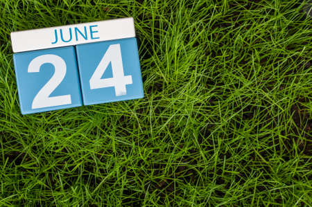 greengrass: June 24th. Image of june 24 wooden color calendar on greengrass lawn background. Summer day, empty space for text.