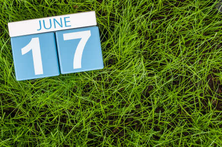 greengrass: June 17th. Image of june 17 wooden color calendar on greengrass lawn background. Summer day, empty space for text.