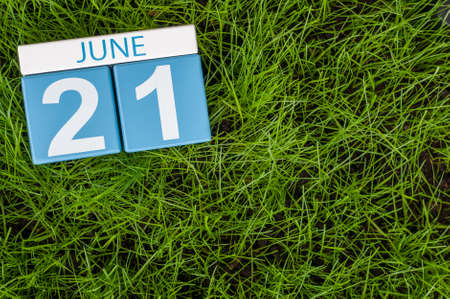 greengrass: June 21st. Image of june 21 wooden color calendar on greengrass lawn background. Summer day, empty space for text.