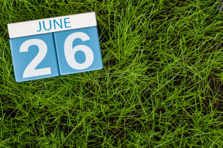 greengrass: June 26th. Image of june 26 wooden color calendar on greengrass lawn background. Summer day, empty space for text.