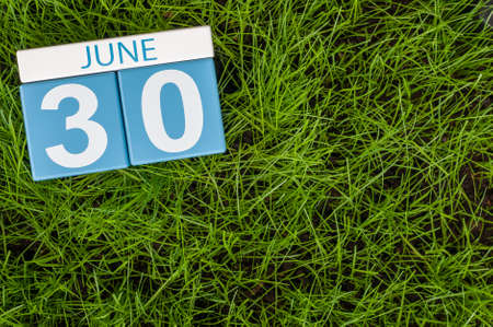 greengrass: June 30th. Image of june 30 wooden color calendar on greengrass lawn background. Summer day, empty space for text.