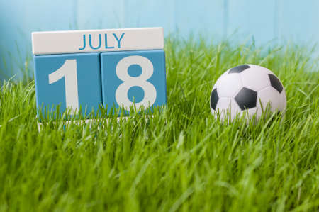 18th: July 18th. Image of july 18 wooden color calendar on greengrass lawn background. Summer day, empty space for text.