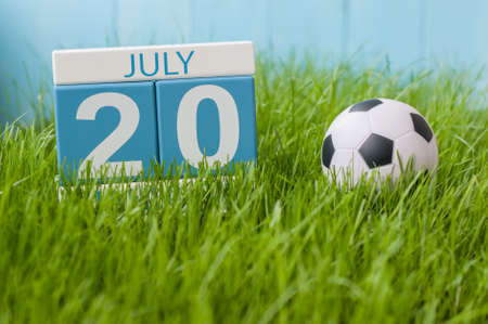 greengrass: July 20th. Image of july 20 wooden color calendar on greengrass lawn background. Summer day, empty space for text.