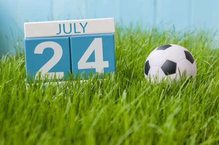 greengrass: July 24th. Image of july 24 wooden color calendar on greengrass lawn background. Summer day, empty space for text.