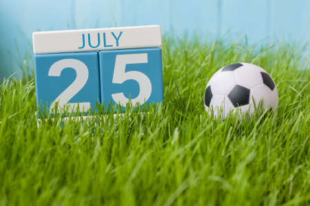 25th: July 25th. Image of july 25 wooden color calendar on greengrass lawn background. Summer day, empty space for text.