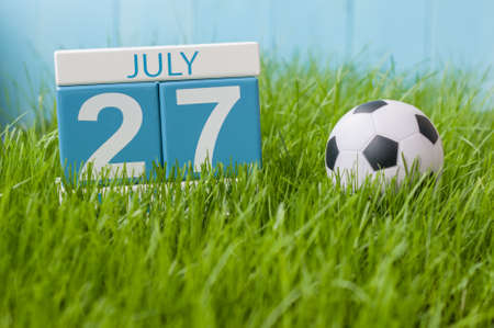 greengrass: July 27th. Image of july 27 wooden color calendar on greengrass lawn background. Summer day, empty space for text.