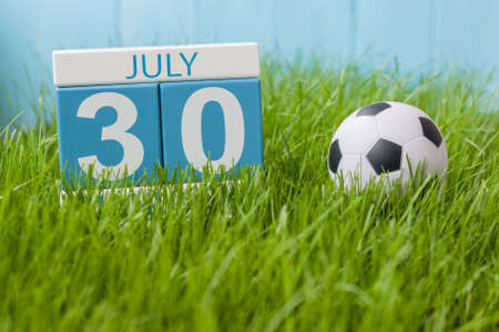 greengrass: July 30th. Image of july 30 wooden color calendar on greengrass lawn background. Summer day, empty space for text.