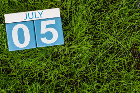 5th: July 5th. Image of july 5 wooden color calendar on green lawn grass background. Summer day. Stock Photo