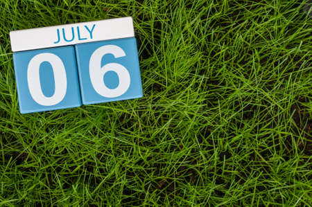 greengrass: July 6th. Image of july 6 wooden color calendar on greengrass lawn background. Summer day, empty space for text. Stock Photo