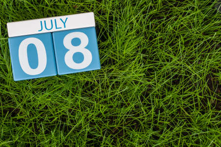 8 years birthday: July 8th. Image of july 8 wooden color calendar on greengrass lawn background. Summer day, empty space for text. Stock Photo