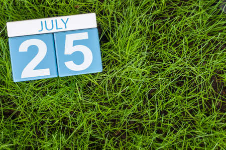 greengrass: July 25th. Image of july 25 wooden color calendar on greengrass lawn background. Summer day, empty space for text.