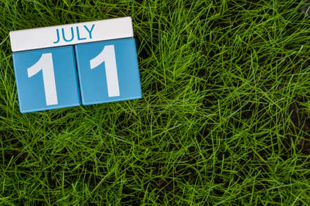 11th: July 11th. Image of july 11 wooden color calendar on greengrass lawn background. Summer day, empty space for text.