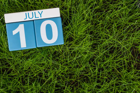 10th: July 10th. Image of july 10 wooden color calendar on greengrass lawn background. Summer day, empty space for text.