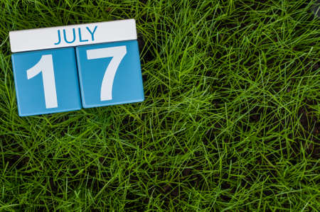 17th: July 17th. Image of july 17 wooden color calendar on greengrass lawn background. Summer day, empty space for text. Stock Photo
