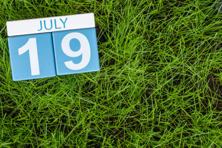 greengrass: July 19th. Image of july 19 wooden color calendar on greengrass lawn background. Summer day, empty space for text.