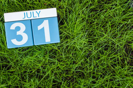 31st: July 31st. Image of july 31 wooden color calendar on greengrass lawn background. Summer day, empty space for text.