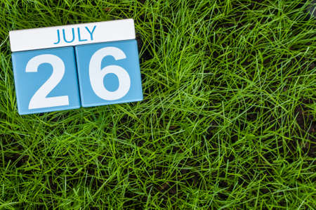 greengrass: July 26th. Image of july 26 wooden color calendar on greengrass lawn background. Summer day, empty space for text.