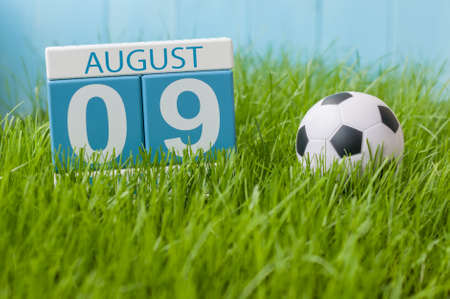 9 ball: August 9th. Image of august 9 wooden color calendar on green grass lawn background with soccer ball. Summer day. Empty space for text. Stock Photo