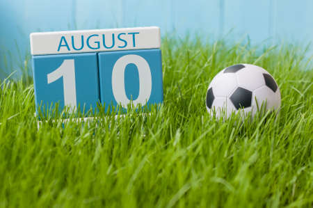 10th: August 10th. Image of august 10 wooden color calendar on green grass lawn background with soccer ball. Summer day. Empty space for text.
