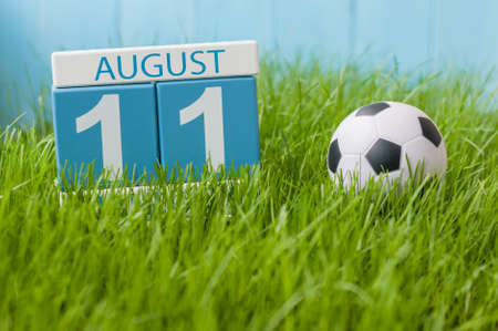 11th: August 11th. Image of august 11 wooden color calendar on green grass lawn background with soccer ball. Summer day. Empty space for text.