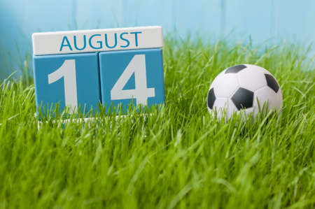 14th: August 14th. Image of august 14 wooden color calendar on green grass lawn background with soccer ball. Summer day. Empty space for text. Stock Photo