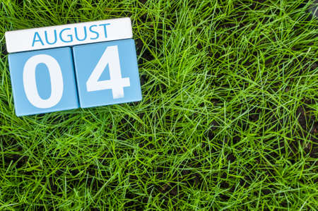 august: August 4th. Image of august 4 wooden color calendar on green grass lawn background. Summer day. Empty space for text. Stock Photo