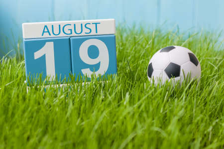 August 19th. Image of august 19 wooden color calendar on green grass lawn background with soccer ball. Summer day. Empty space for text.