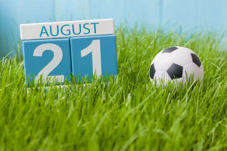 August 21st. Image of august 21 wooden color calendar on green grass lawn background with soccer ball. Summer day. Empty space for text.