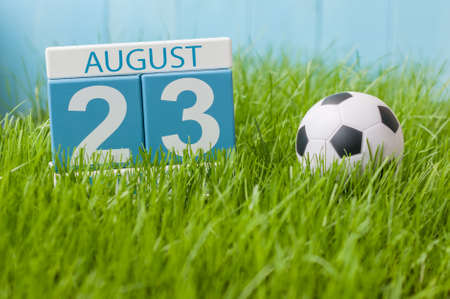 important date: August 23rd. Image of august 23 wooden color calendar on green grass lawn background with soccer ball. Summer day. Empty space for text. Stock Photo