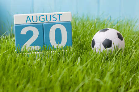 August 20th. Image of august 20 wooden color calendar on green grass lawn background with soccer ball. Summer day. Empty space for text.
