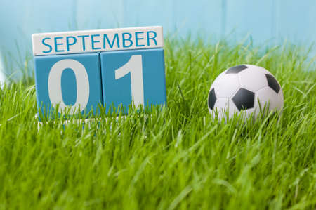 first year student: September 1st. Image of september 1 color calendar on green lrass lawn background. Autumn day. Empty space for text. Back to school time.