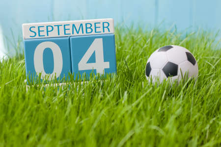 personal organiser: September 4th. Image of september 4 wooden color calendar on green grass lawn background. Autumn day. Empty space for text. Stock Photo