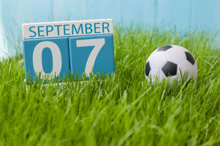 sep: September 7th. Image of september 7 wooden color calendar on green grass lawn background. Autumn day. Empty space for text.