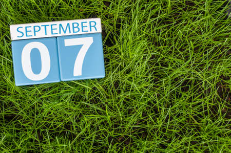 empty space for text: September 7th. Image of september 7 wooden color calendar on green grass lawn background. Autumn day. Empty space for text.