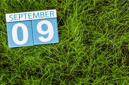 september 9th: September 9th. Image of september 9 wooden color calendar on green grass lawn background. Autumn day. Empty space for text. International Beauty Day.