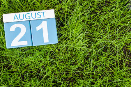 next day: August 21st. Image of august 21 wooden color calendar on green grass lawn background with soccer ball. Summer day. Empty space for text.
