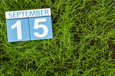 15th: September 15th. Image of september 15 wooden color calendar on green grass lawn background.