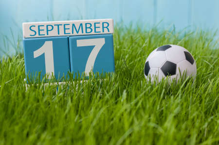 17th: September 17th. Image of september 17 wooden color calendar on green grass lawn background.