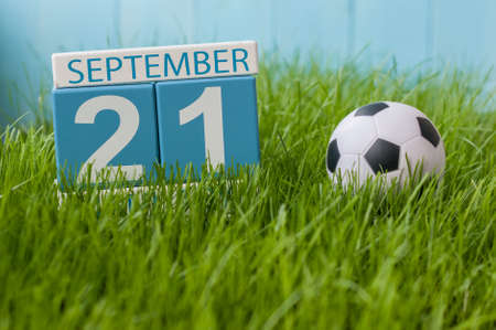 first year student: September 21st. Image of september 21 wooden color calendar on green grass lawn background. Stock Photo