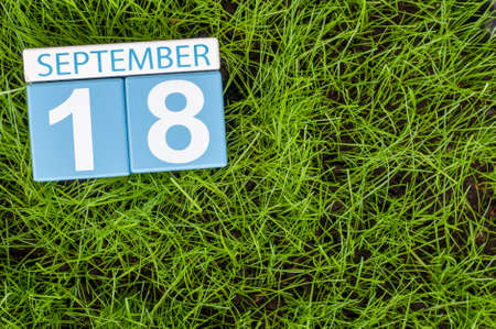 18th: September 18th. Image of september 18 wooden color calendar on green grass lawn background.