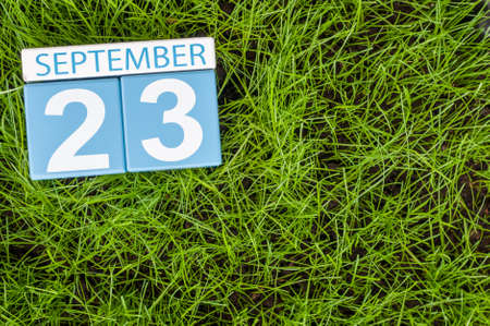 20 23 years: September 23rd. Image of september 23 wooden color calendar on green grass lawn background. Stock Photo