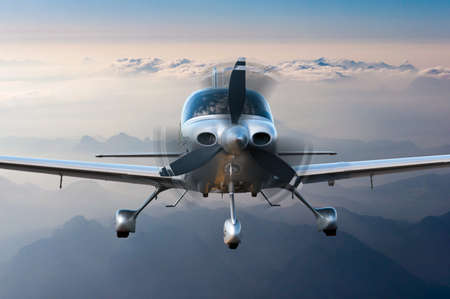 private plane: Private plane or aircraft flight surrounded by mountains and rocks. Stock Photo