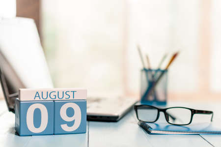 August 9th. Day 9 of month wooden color calendar on business office background.