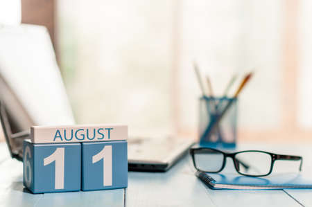 11th: August 11th. Day 11 of month, wooden color calendar on freelance workplace background. Stock Photo