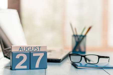 workaholic: August 27th. Day 27 of month, wooden color calendar on workaholic workplace background.