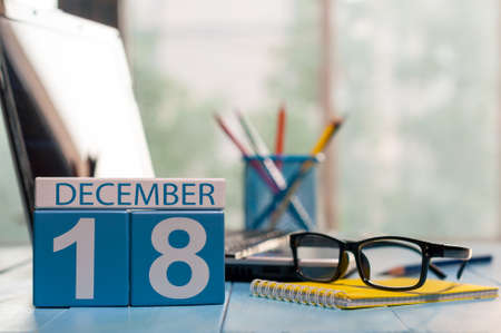 December 18th. Day 18 of month calendar on office worker workplace background.