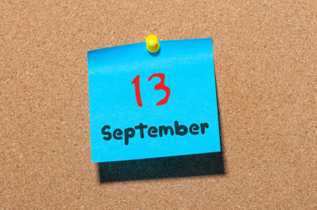 13th: September 13th. Day 13 of month, color sticker calendar on notice board. Autumn time. Empty space for text.