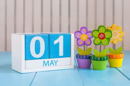 1 mei. Afbeelding van 1 mei houten kleur kalender op een witte achtergrond met bloemen. lentedag, lege ruimte voor tekst. Dag van de arbeid. Stockfoto